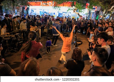 Hanoi, Vietnam - March 12, 2018: Crowd gathers to watch street performance and woman dancing energetically in Old Quarter