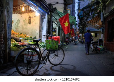 Hanoi, Vietnam - March 14, 2018: Vintage bicycle with shopping bags in front of back alley produce shop