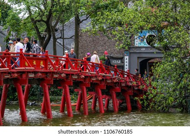 Hanoi, Vietnam - March 15, 2018: Tourists walking on the red bridge leading to Den Ngoc Son temple on the lake in Hanoi. Credit: Dino Geromella/Shutterstock