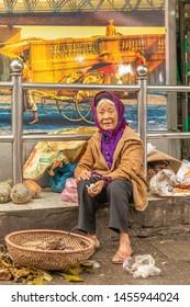 Hanoi / Vietnam - March 16 2019:  Old vietnamese woman trying to make money.