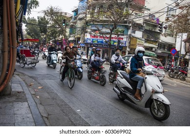 HANOI, VIETNAM - MARCH 2, 2017: Unidentified people on the street of Hanoi, Vietnam. At Hanoi, motorbikes have overtaken bicycles as the main form of transportation.