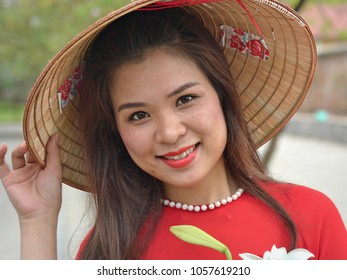 HANOI, VIETNAM - MARCH 28, 2018: Young Vietnamese woman in red wears a traditional Asian conical straw hat, holds the brim of the hat with her right hand, and poses for the camera, on March 28, 2018.
