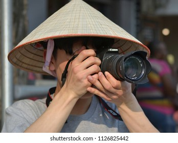 HANOI, VIETNAM - MARCH 4, 2018: Young male Vietnamese street photographer wears an Asian conical straw hat and takes a snapshot with his Canon DSLR camera, on March 4, 2018.