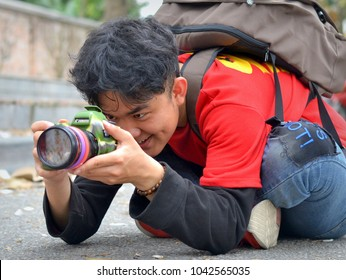 HANOI, VIETNAM - MARCH 6, 2018: Young professional Vietnamese photographer takes portrait photographs with a Canon DSLR 6D in the vicinity of Hanoi's Bac Son Monument, on March 6, 2018.