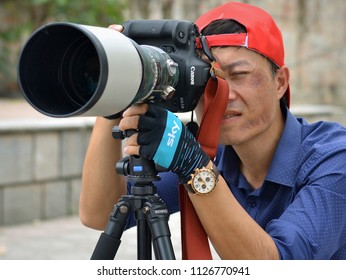 HANOI, VIETNAM - MARCH 6, 2018: Professional Vietnamese portrait and event photographer takes outdoor photographs with a DSLR camera Canon EOS 1DX (front view), on March 6, 2018.