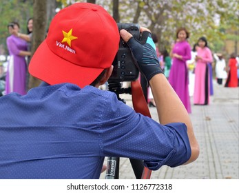 HANOI, VIETNAM - MARCH 6, 2018: Professional Vietnamese portrait and event photographer takes outdoor photographs with a DSLR camera Canon EOS 1DX (rear view), on March 6, 2018.