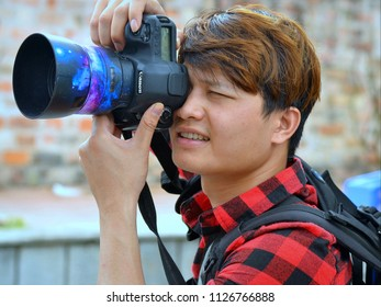 HANOI, VIETNAM - MARCH 7, 2018: Young Vietnamese event photographer takes a photo with a Canon EOS 5D DSLR camera, on March 7, 2018.