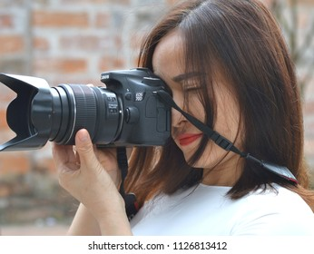 HANOI, VIETNAM - MARCH 8, 2018: Beautiful, young female Vietnamese street photographer takes a photo with a Canon 70D DSLR camera, on March 8, 2018.