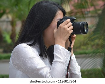 HANOI, VIETNAM - MARCH 8, 2018: Young Vietnamese woman wears a white traditional Vietnamese dress and takes a photo with a Canon DSLR camera, on March 8, 2018.
