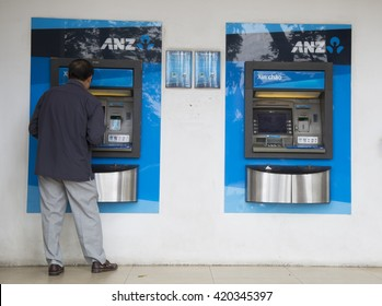 Hanoi, Vietnam - May 14, 2016: Asian man making a transaction at an automatic teller machine (ATM) of ANZ commercial bank in Hanoi capital. ANZ is one of Australia's four largest banks.