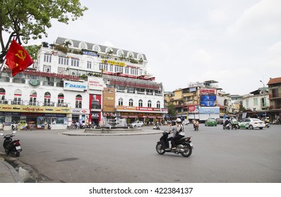 Hanoi, Vietnam - May 14, 2016: Motorcycle and cyclo running on Dong Kinh Nghia Thuc square in the center of Hanoi nearby Hoan Kiem (Sword) lake and 36 old quarter streets.