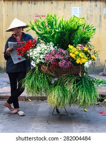 HANOI, VIETNAM - May 2, 2015: An unidentified woman selling flowers on the street in the early morning.