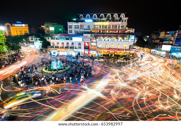 HANOI, VIETNAM - MAY 21, 2016: People and vehicles light trails crowd on busy intersection locating next to Hoan Kiem lake in old quarter of Hanoi capital at night.