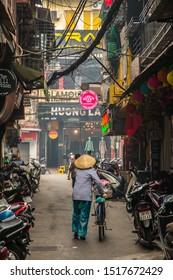 HANOI, VIETNAM, MAY 27, 2018: Unidentified woman rides bicycle along a street of Hanoi, Vietnam