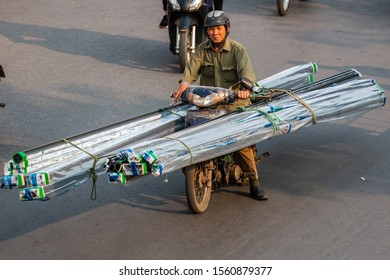 HANOI, VIETNAM, MAY 27, 2018: Vietnamese driving a motorbike and transporting a lot of packages. This is a typical vietnam transport with motorcycle or scooter