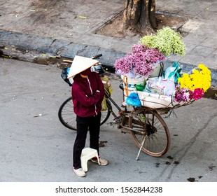 HANOI, VIETNAM, MAY 27, 2018: flowers seller with a bicycle on the streets of Hanoi, Vietnam