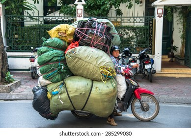 HANOI, VIETNAM, NOV 17, 2013: Unidentified woman drives overloaded motorcycle on the street of Hanoi on November 17, 2013