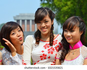 HANOI, VIETNAM - NOV 2, 2012: Three beautiful young Vietnamese girls in traditional dresses (ao dai) pose for the camera in front of the Ho Chi Minh mausoleum, on Nov 2, 2012.