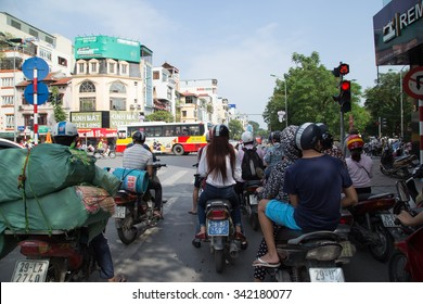 HANOI, VIETNAM - NOV 22, 2015: Unidentified motorbike drivers stopping at the red light traffic in Hanoi. Traffic is one of the most serious matter in Vietnam with many vehicles on narrow streets.