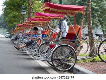 Hanoi, Vietnam - Nov 22, 2015: Cyclo drivers preparing to pick up passenger by lining up on row at an old street. Cyclo is one of the most favorite vehicles for tourist when come to Vietnam's cities.