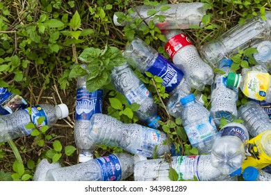 Hanoi, Vietnam - Nov 24, 2015: Crushed plastic bottles of mineral water and bottle caps on grass in Park, Vietnam, concept of environmental protection, littering of environment.
