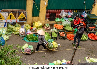 HANOI, VIETNAM - November 20, 2019: Street Vendors at Long Bien Market as Seen from Above on the Long Bien Bridge at Sunrise