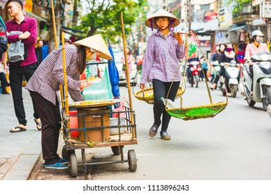 HANOI, VIETNAM - NOVEMBER 21, 2017: Street food vendor, wearing typical Asian coolie hat and preparing fried food with other peddler walking past and mopeds on the busy street