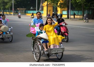 Hanoi, Vietnam - Oct 16, 2016: Vietnamese girl wears traditional long dress Ao Dai going by Cyclo (pedicab) on Hanoi street