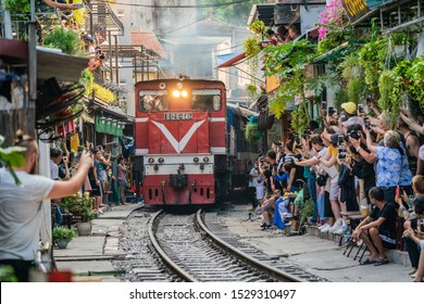 HANOI, VIETNAM - OCT 6, 2019 : View of train passing through a narrow street of the Hanoi Old Quarter. Tourists taking pictures of hurtling train. The Hanoi Train Street is a popular attraction.