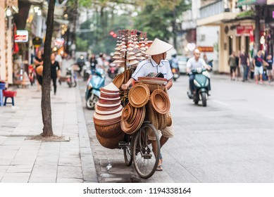 Hanoi, Vietnam - October 15, 2016. Street vendor with a bicycle on the streets of Hanoi, Vietnam. Selling traditional hats in the middle of busy traffic in the capital city.