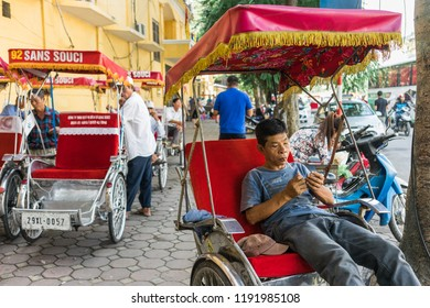 Hanoi, Vietnam - October 16, 2016. Traditional cyclo driver taking a smoke break while waiting for passengers on the streets of Hanoi, Vietnam. The cyclo is a three-wheel bicycle taxi.