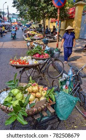 HANOI, VIETNAM - OCTOBER 18, 2015: Lady Walking Through the Hanoi Old Town Buying Fruit