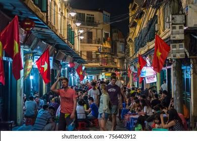 HANOI, VIETNAM - OCTOBER 2014 - Tourists enjoying beer on busy Hanoi street full of bars