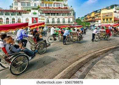 Hanoi, Vietnam - October 27, 2017: Hanoi old quarter main square, rickshaw drivers carrying tourists around town.