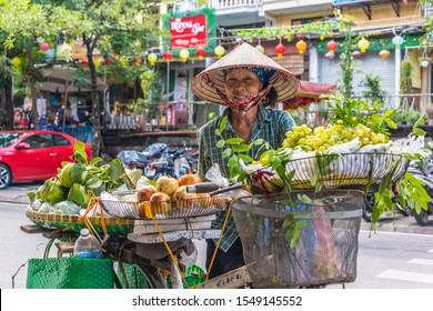 HANOI, VIETNAM - SEP 19, 2019: Vietnamese woman selling fruit on a bike in the old town of Hanoi, Vietnam
