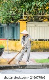 HANOI, VIETNAM - SEP 23, 2014: Unidentified Vietnamese woman cleans the street. 92% of Vietnamese people belong to the Viet ethnic group