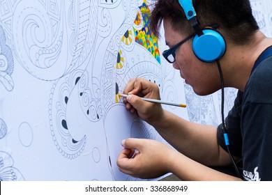 Hanoi, Vietnam - Sep 29, 2015: Young man artist drawing on large paper at street in Hanoi, Vietnam