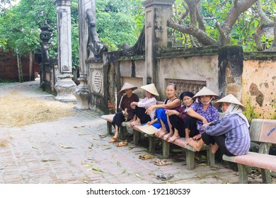 HANOI, VIETNAM - SEPT, 29: Old women chatting at the gate of ancient temple in Duong Lam village, Hanoi, Vietnam. on September 29, 2013.