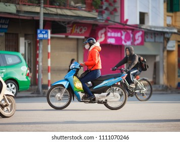 Hanoi, Vietnam-December 17, 2013. Young woman rides on motorbike in early morning and listen to the music, also wears a mask to protect from polliution on December 17, 2013 in Hanoi city, Vietnam.