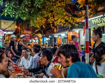 HANOI/VIETNAM - 09 15 14: Locals and tourists drink freshly brewed beer in the streets of Hanoi