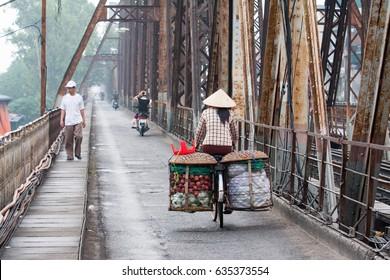 Hanoi,VietNam May 07,2017: Back view of street woman vendor carrying fruit on bike on Long Bien ancient metal bridge