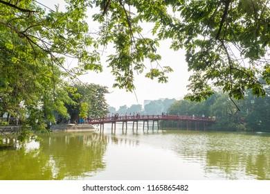 "Hanoi,Vietnam - November 2,2017 : Red Huc bridge in Hoan Kiem Lake,Hanoi. Hoan Kiem Lake meaning ""Lake of the Returned Sword"". People can seen exploring around it."