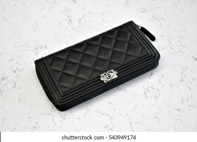 HANOVER, USA - DECEMBER 27, 2016: A black Chanel boyfriend wallet on a white marble surface.