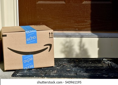 HANOVER, USA - DECEMBER 27, 2016: An Amazon Prime package delivered to the front door of a residential home. Amazon is a popular American electronic commerce and cloud computing company.
