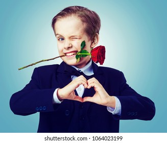 hansome boy wearing a black suit with rose in his teeth, isolated against studio background