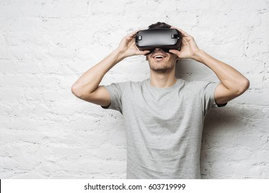 c7f2ea04145 Hansome european male in gray t-shirt experiencing virtual reality using VR  headset glasses.
