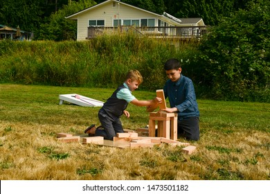 Hansville, Washington/ USA - July 14, 2019 - Kids played big Jenga sticks in the park during a wedding reception.