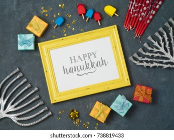 Hanukkah background with photo frame, menorah and gift box over blackboard. View from above. Flat lay