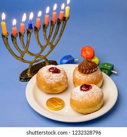 Hanukkah celebration concept with sufganiyot, chocolate coin, wooden  dreidels  and menorah.
