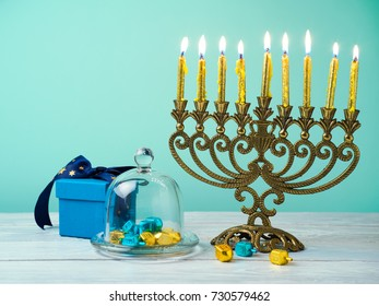 Hanukkah celebration with menorah, golden candles, gift box and spinning top